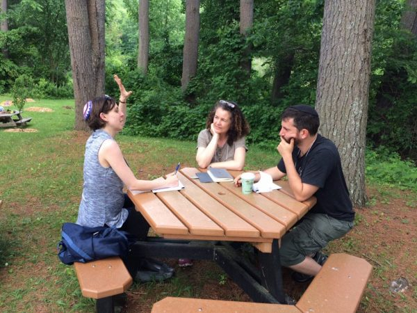 Three people talking, sitting around a picnic table, surrounded by trees