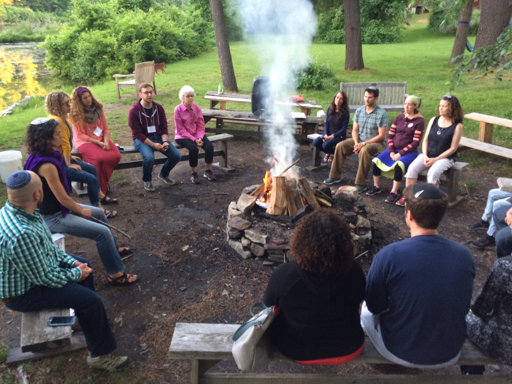 CLI fellows sitting on benches around a fire